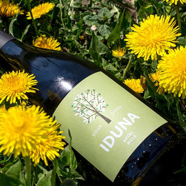 Eine Flasche Iduna Apfel-Cider inmitten von Blumen.
