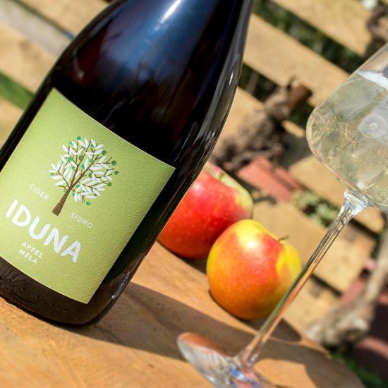 Eine Flasche Iduna Apfel-Cider mit Glas.