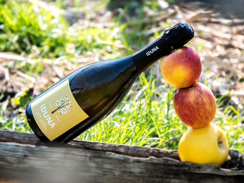 Eine Flasche Iduna mit Quitte, mit dekorativen Äpfeln.