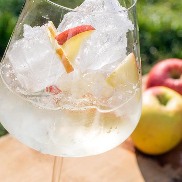 Ein Glas Iduna Apfel-Cider mit Äpfel im Hintergrund.